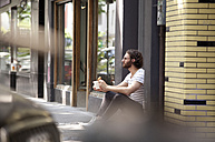 Young man with coffee mug and croissant sitting at entrance of a coffee shop - MFRF00914