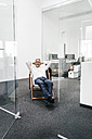 Smiling mature businessman relaxing on deck chair in office - KNSF02110