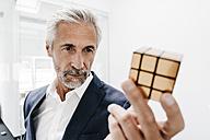 Mature businessman in office examining Rubik's Cube - KNSF02113