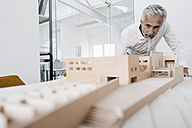 Mature businessman examining architectural model in office - KNSF02116