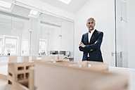 Mature businessman with architectural model in office - KNSF02125
