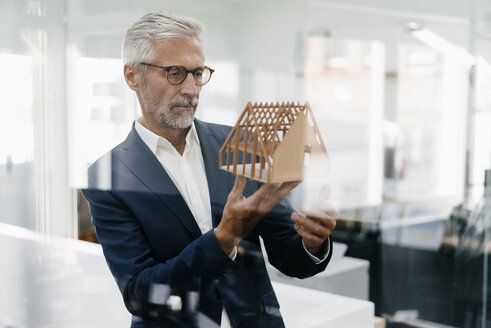 Mature businessman examining architectural model in office - KNSF02134