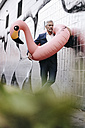 Mature businessman outdoors with inflatable flamingo - KNSF02137