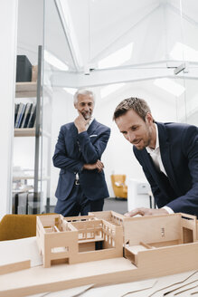 Two businessmen examining architectural model in office - KNSF02143
