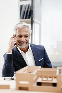 Mature businessman examining architectural model in office - KNSF02146