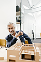 Portrait of smiling mature businessman with architectural model in office - KNSF02149