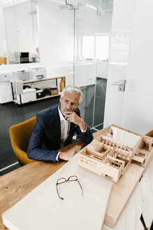Mature businessman with architectural model in office - KNSF02152