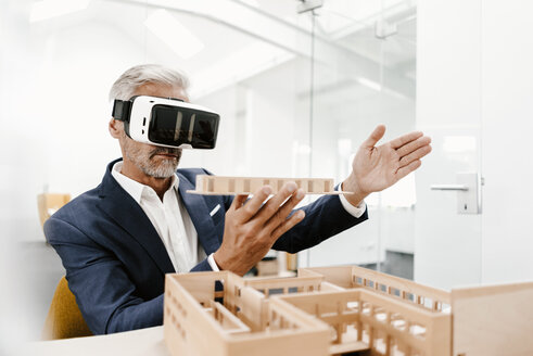 Mature businessman with architectural model in office wearing VR glasses - KNSF02158