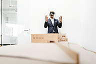 Mature businessman with architectural model in office wearing VR glasses - KNSF02161
