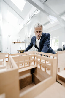 Mature businessman examining architectural model in office - KNSF02170