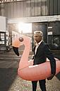 Mature businessman on the street with inflatable flamingo - KNSF02179