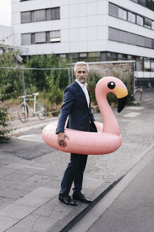 Mature businessman on the street with inflatable flamingo - KNSF02182