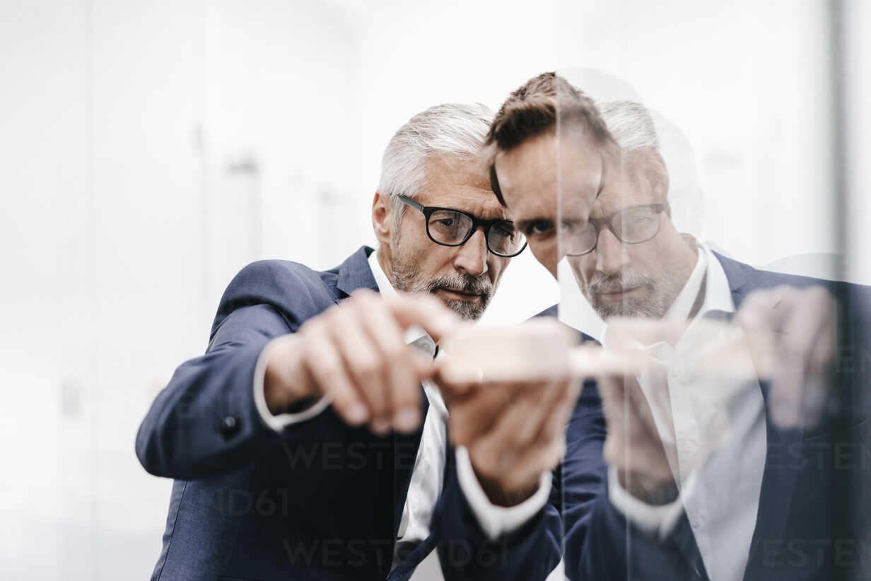 Two businessmen examining architectural model at glass pane - KNSF02185 - Kniel Synnatzschke/Westend61