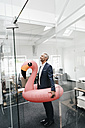 Businessman in office with inflatable flamingo - KNSF02191