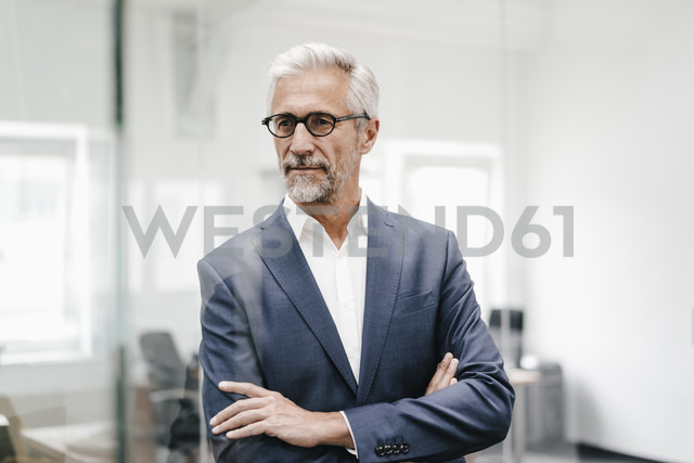 Confident mature businessman in office - KNSF02206
