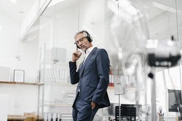 Mature businessman in office wearing headphones - KNSF02209