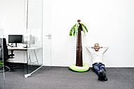 Smiling mature businessman sitting next to inflatable palm tree in office - KNSF02215