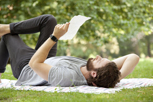 Man lying on blanket in a park reading a letter - MFRF00924