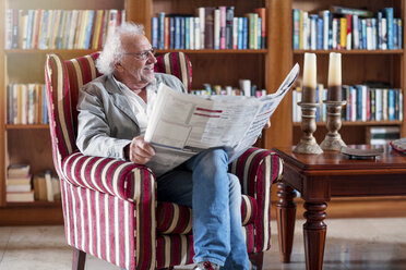 Senior man sitting in library, reading newpaper - ZEF14201