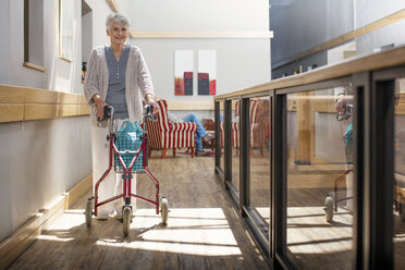 Senior woman in retirement home pushing wheeled walker - ZEF14225