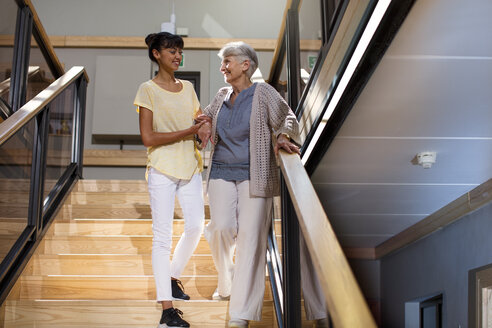 Nurse helping senior woman to walk down the stairs - ZEF14228