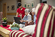 Seniors at retirement home looking at photo albums - ZEF14234