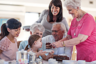 Grandparents celebrating a birthday with their granddaughter, eating chocolate cake - ZEF14255