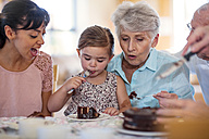 Grandparents celebrating a birthday with their granddaughter, eating chocolate cake - ZEF14258