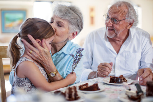 Grandparents celebrating a birthday with their granddaughter, eating chocolate cake - ZEF14264