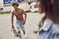 Young man with skateboard running to his girlfriend - SUF00246