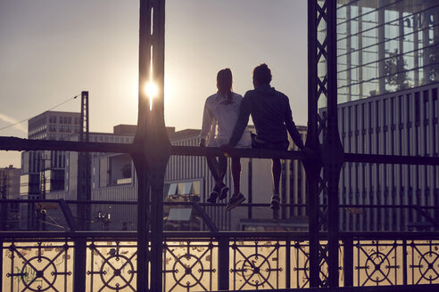 Germany, Munich, Young couple sitting on bridge, enjoying sunset - SUF00261