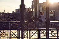 Germany, Munich, Young couple sitting on bridge, enjoying sunset - SUF00264