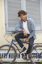 Young man sitting on bicycle, looking at camera - SUF00276