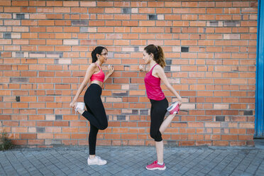 Two active women stretching at a brick wall - JPF00257