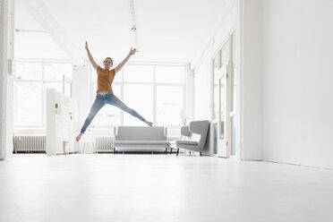 Woman jumping in the air in a loft - KNSF02232