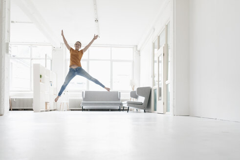 Woman jumping in the air in a loft - KNSF02232