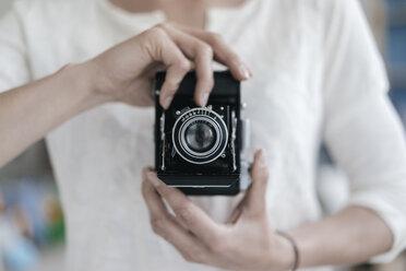 Woman's hands holding vintage camera - KNSF02235