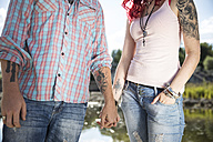 Tattooed young couple holding hands, partial view - MAEF12384