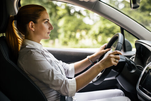 Businesswoman driving car - MOMF00191