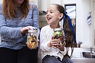 Laughing little girl with preserving jar of mixed salad sitting beside her mother - IGGF00005