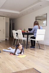 Little girl lying on floor drawing a picture while her mother working on laptop in the background - IGGF00014