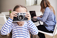 Little girl taking picture with camera while her mother working on laptop in the background - IGGF00017