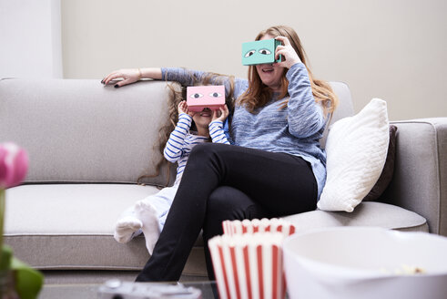 Mother and little daughter sitting on the couch having fun with Virtual Reality Glasses - IGGF00023