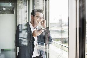 Portrait of confident businessman on the phone looking through window - UUF11219