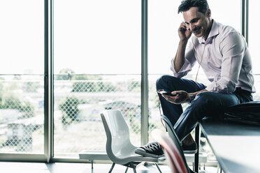 Businessman in office sitting on desk, using smartphone - UUF11258