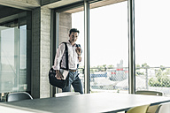 Businessman standing by window, entering the office - UUF11261