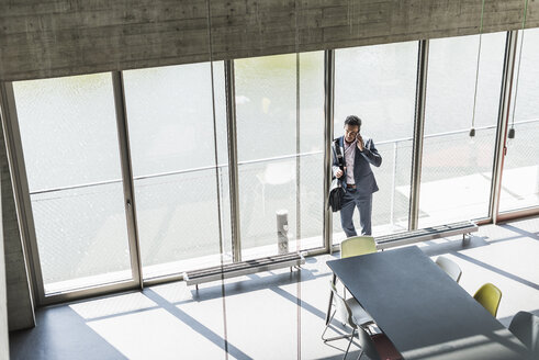 businessman standing by window, making a phone call - UUF11267