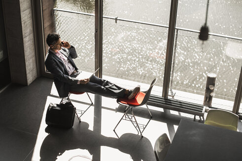 Businessman sitting at the window with feet up, working on laptop and making a call - UUF11270