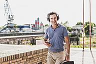 Businessman walking in the city, using smartphone and headphones - UUF11288