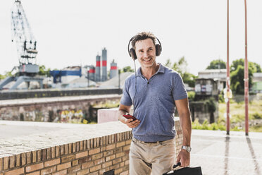 Businessman walking in the city, using smartphone and headphones - UUF11288